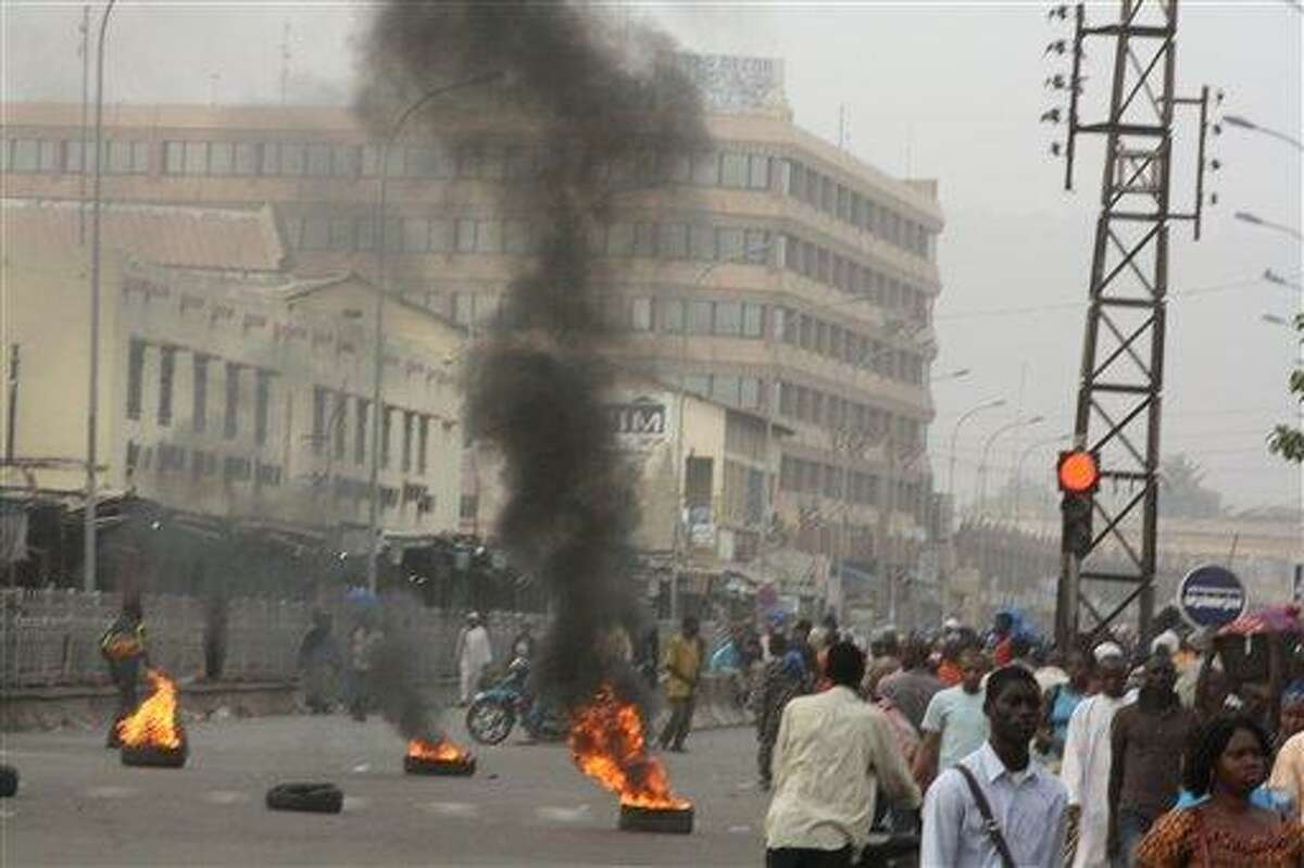 Civilians walk past burning tires lit in support of mutinying soldiers, in Bamako, Mali, Wednesday. Gunshots could still be heard in the Malian capital late Wednesday, hours after angry troops started a mutiny at a military base near the presidential palace. Associated Press