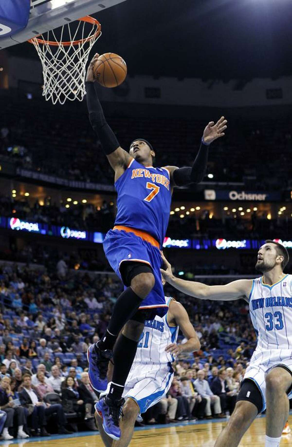 New York Knicks forward Carmelo Anthony (7) drives to the basket ahead of New Orleans Hornets forward Ryan Anderson (33) and guard Greivis Vasquez (21) during the first half of an NBA basketball game in New Orleans, Tuesday, Nov. 20, 2012. (AP Photo/Gerald Herbert)