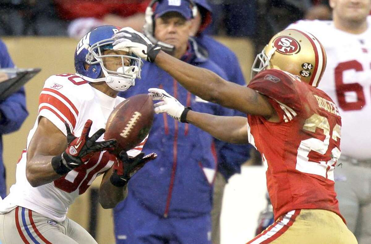 New York Giants' Victor Cruz catches a pass in front of New York Giants' Derrick Martin (22) during the first half of the NFC Championship NFL football game Sunday, Jan. 22, 2012, in San Francisco. (AP Photo/Julie Jacobson)