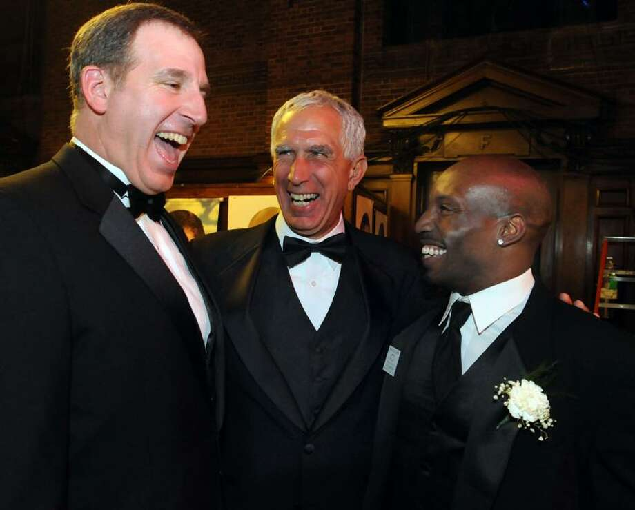 Cheshire football coach Mark Ecke, left, at Yale for the 2011 Walter Camp dinner with UConn coach Paul Pasqualoni, center, and Cheshire assistant coach Kyle McIntosh, right, announced his resignation on Monday night. (Mara Lavitt/Register file photo)