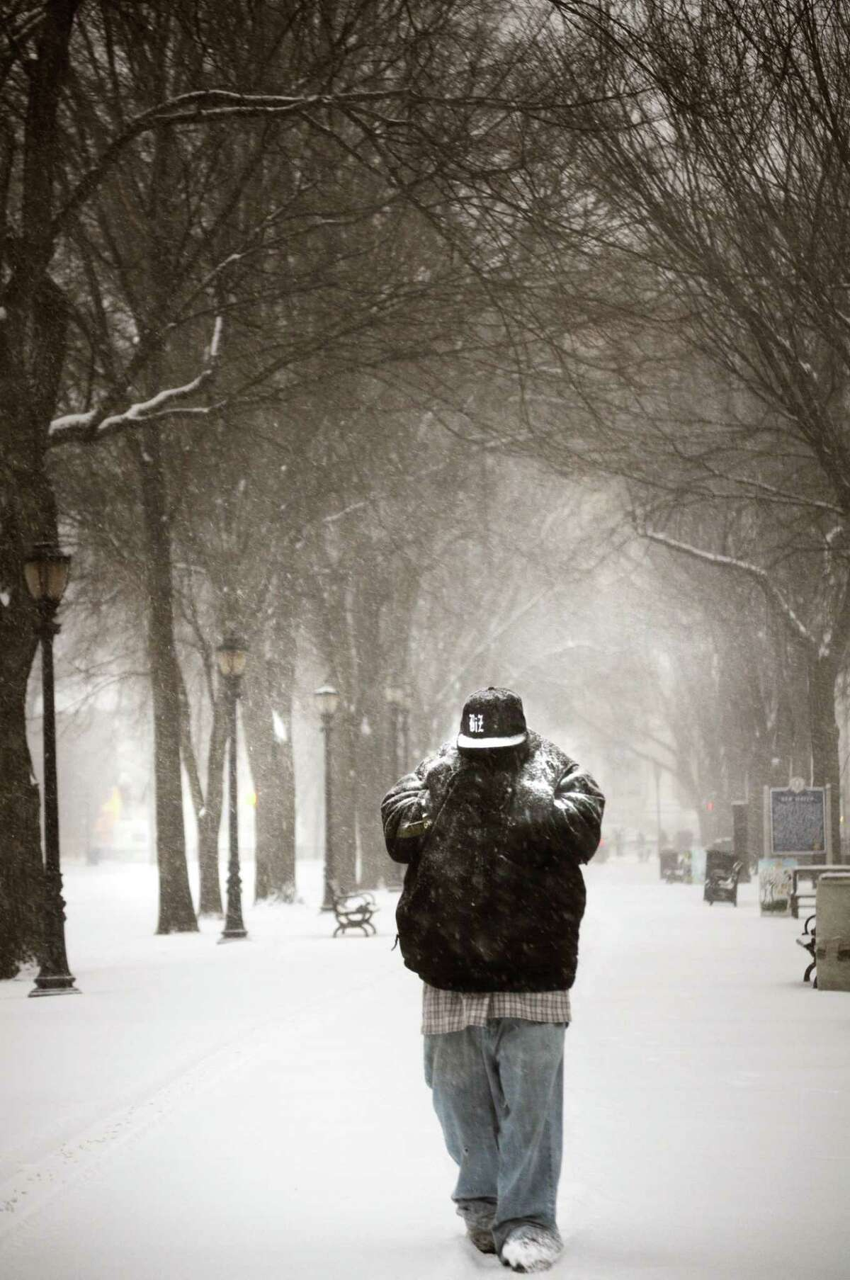 Marquis Jones of New Haven makes his way across the New Haven Green during the morning snow storm. Melanie Stengel/Register