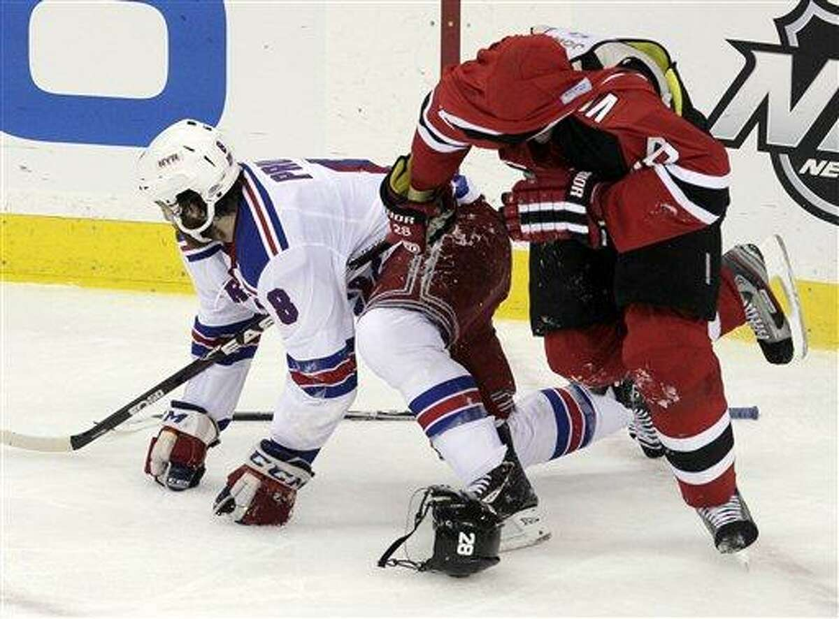 New Jersey Devils defenseman Anton Volchenkov, right, of Russia, skates away with his jersey over his head after tussling with New York Rangers right wing Brandon Prust during the first period of game 3 of an NHL hockey Stanley Cup Eastern Conference final playoff series, Saturday, May 19, 2012, in Newark, N.J. (AP Photo/Peter Morgan)