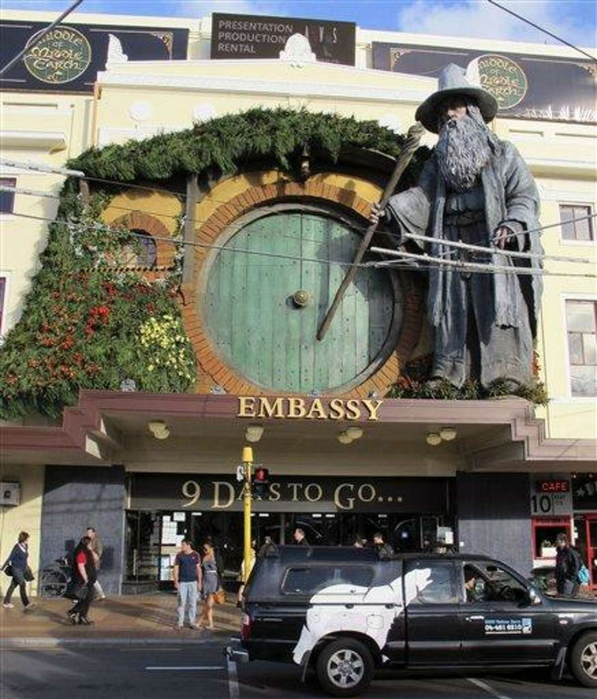 People walk by the Embassy Theater where a giant statue of the character Gandalf from the upcoming movie