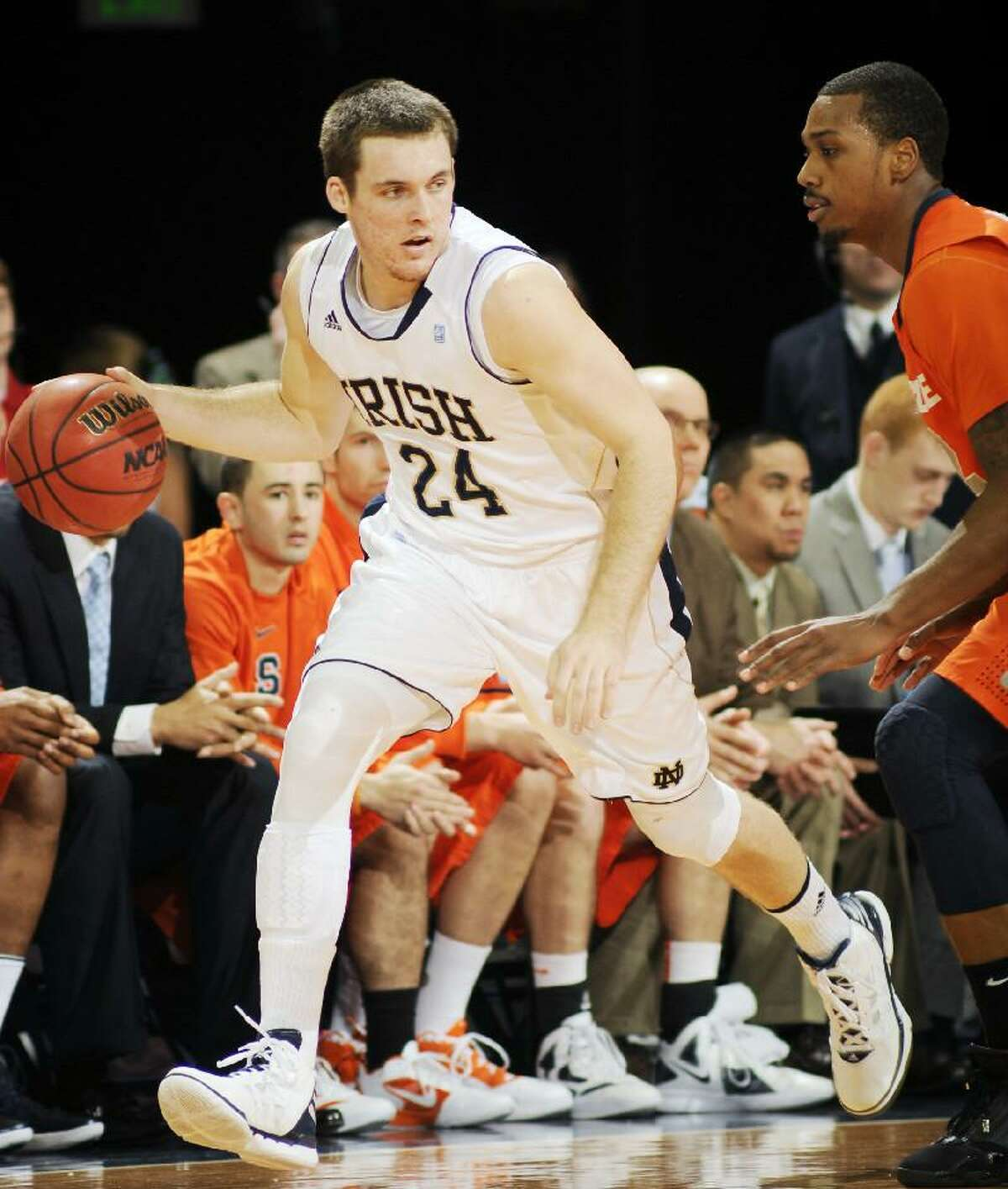 ASSOCIATED PRESS Notre Dame guard Pat Connaughton (24) drives the lane as Syracuse forward Kris Joseph pursues during the first half of Saturday's game in South Bend, Ind.