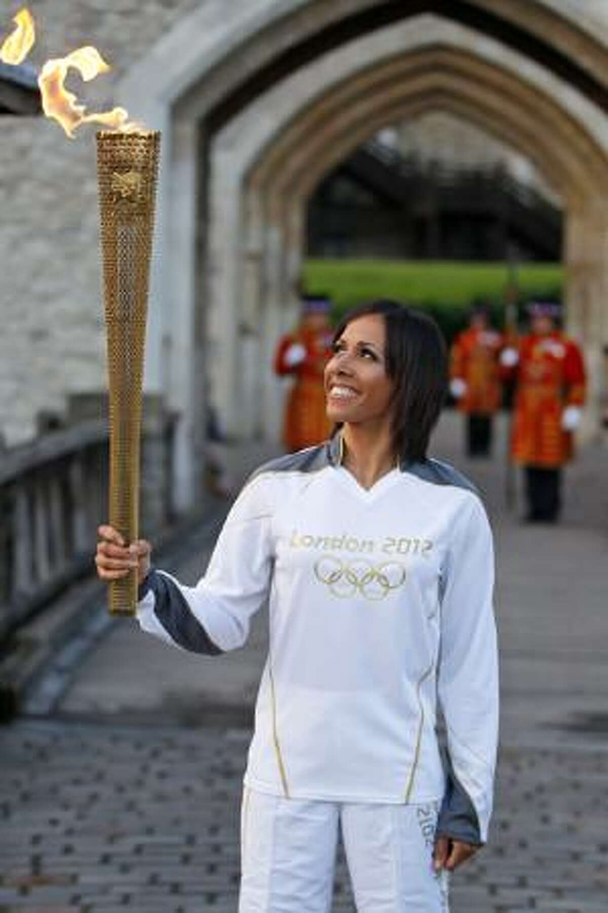 ASSOCIATED PRESS British retired champion Dame Kelly Holmes poses for the photographers with the Olympic flame at the Tower of London on Friday. The Olympic torch arrived in London after it was carried around England in a relay of torchbearers to make its way to the London 2012 Olympic Games opening ceremony on July 27.