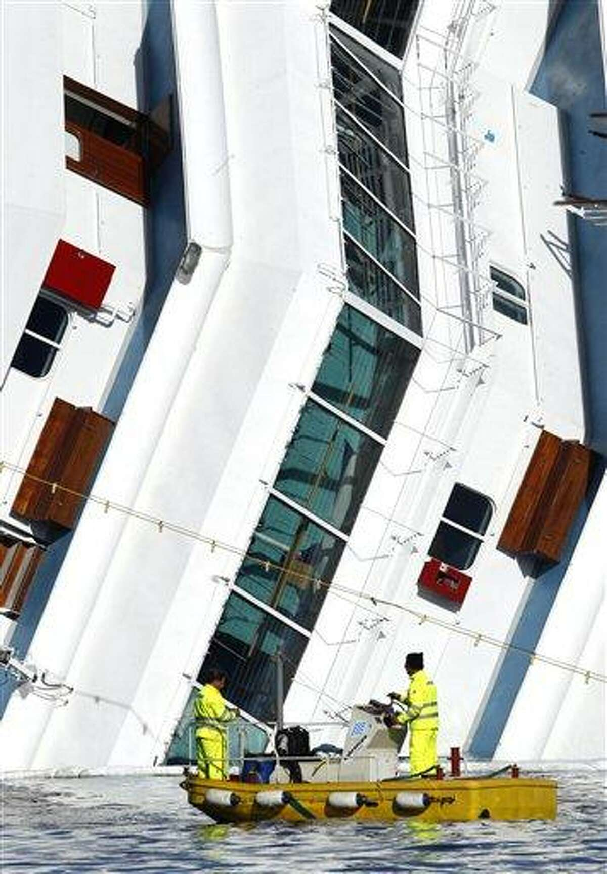Fuel spill experts work around the grounded cruise ship Costa Concordia off the Tuscan island of Giglio, Italy, Saturday. The search resumed for 21 missing passengers. Associated Press