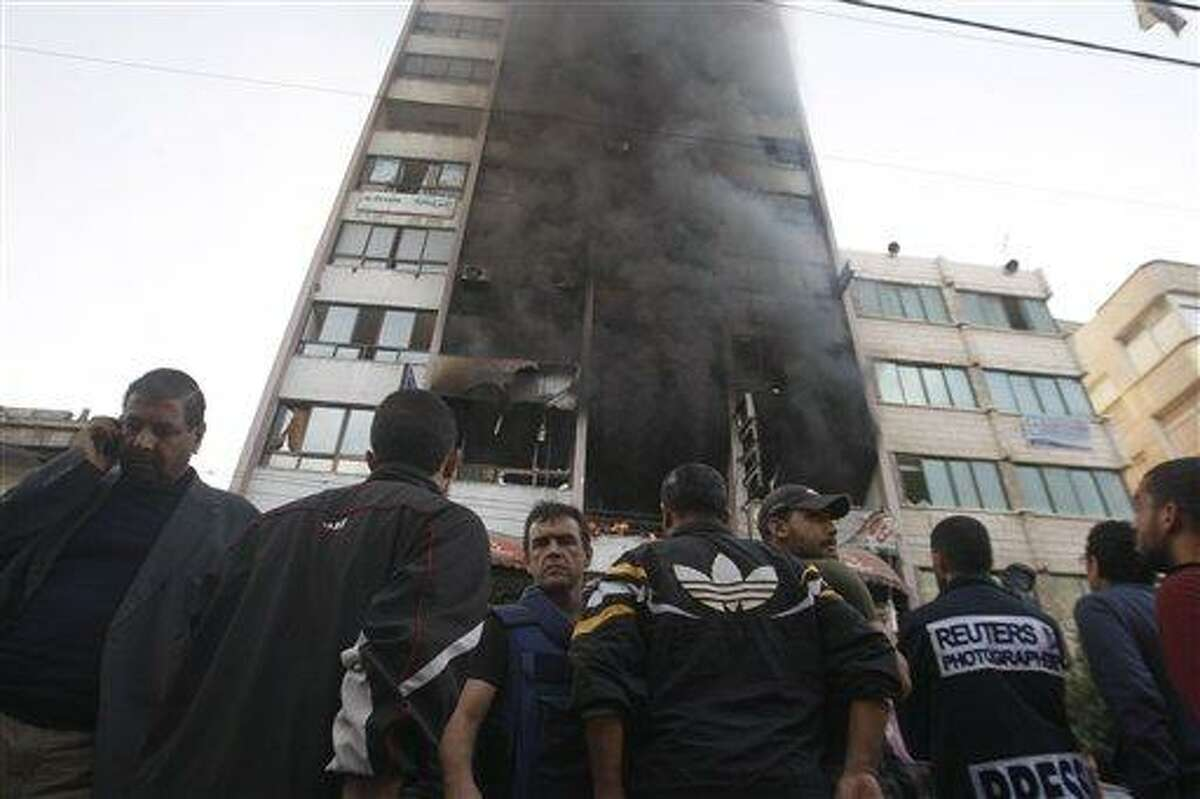 People stand in front of a high rise housing media organizations Monday in Gaza City. Israeli military struck the building for the second time in two days. The Hamas TV station, Al Aqsa, is located on the top floor. Associated Press