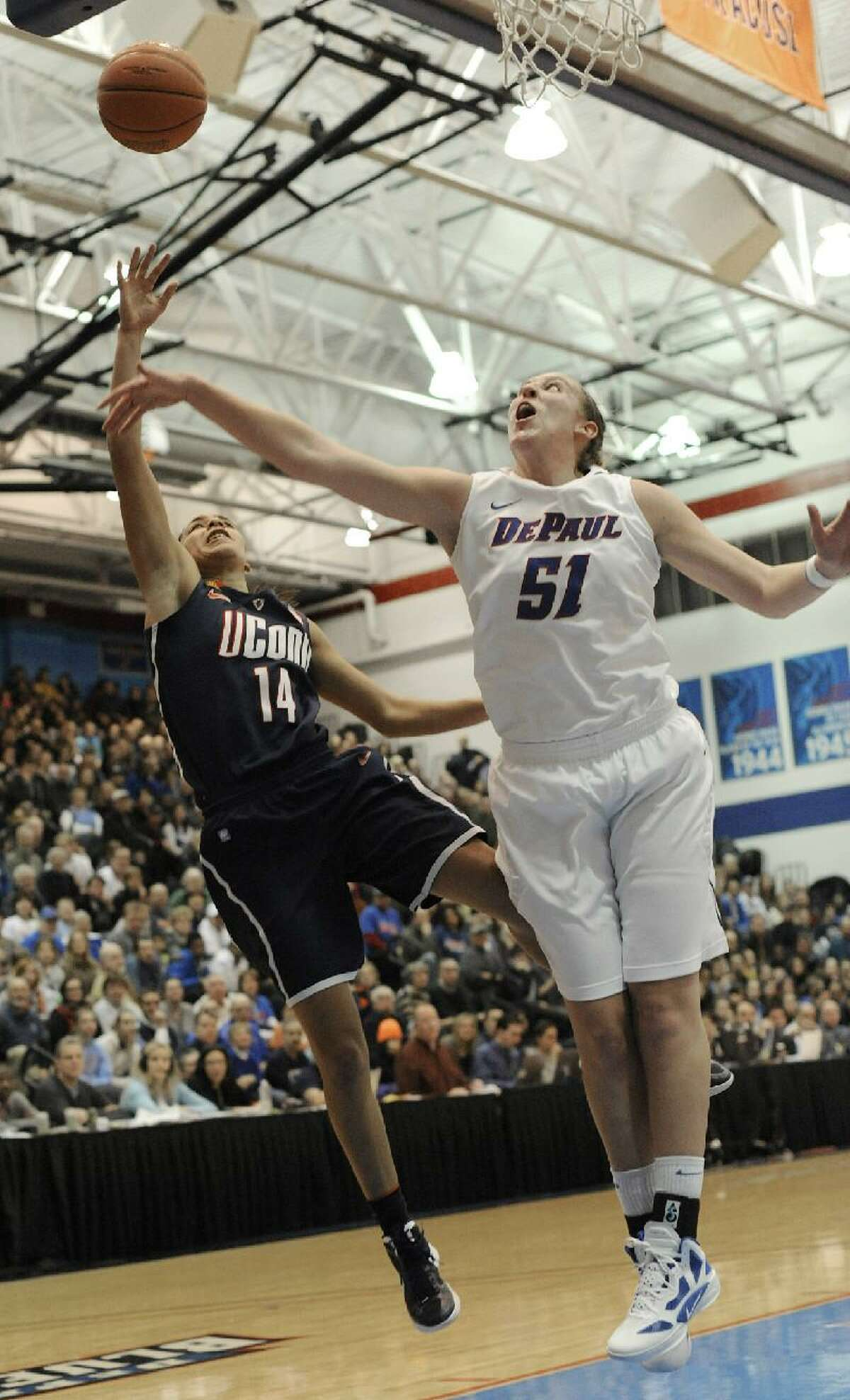 ASSOCIATED PRESS Connecticut's Bria Hartley left, goes up for a shot against DePaul's Katherine Harry right, in the first half during Saturday's game in Chicago. The Huskies won 88-44.