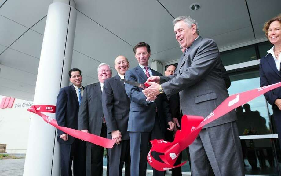 In this file photo, from left to right, Orange Selectman John Carangelo, Edward Drew, senior director of corporate projects for UIL Holdings Corp. and state Rep. Paul Davis watch James Torgerson, president and CEO of UIL Holdings Corp., and Anthony Vallillo, Chief Operating Officer and Executive Vice President of UIL Holdings Corp., cut a ribbon at the new United Illuminating corporate headquarters on Marsh Hill Road in Orange. At right is Orange selectman Judy Williams. Arnold Gold/Register