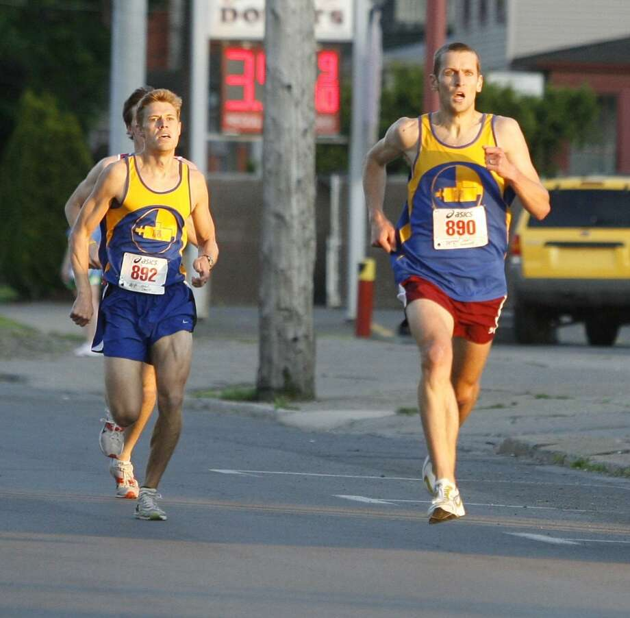 """Dispatch Staff Photo by JOHN HAEGER <a href=""""http://twitter.com/oneidaphoto"""">twitter.com/oneidaphoto</a> Sam  Mackenzie (890) pulls ahead of training partner Sam Hicks to win the 13th annual the Wilber-Duck Mile in the City of Oneida on Friday, May 18, 2012."""