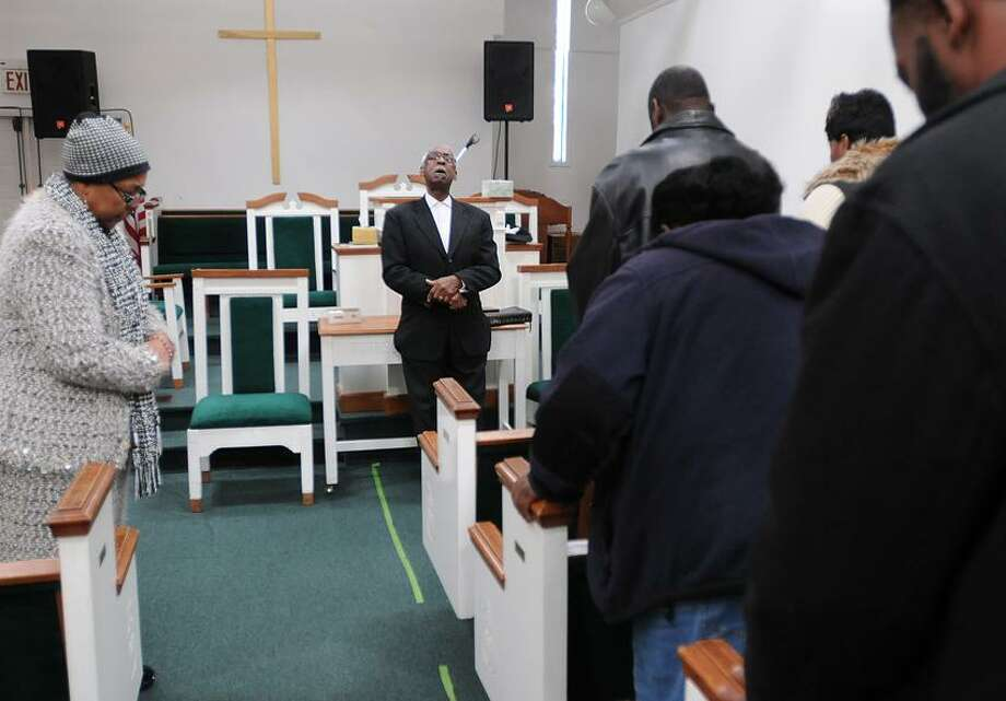 House of God Church Pastor Hilda Alston, left,  and Assistant Pastor Melvin Alston, second from left, lead family and friends of Aaron Powell in prayer for Michael Lieto and the Lieto family during a short worship service Friday, November 16, 2012 at the New Haven church on Division street. Aaron Powell was arraigned Wednesday on manslaughter charges in the stabbing of Michael Lieto in East Haven Tuesday over a dispute stemming from a gold chain. Photo by Peter Hvizdak / New Haven Register Photo: New Haven Register / ©Peter Hvizdak /  New Haven Register
