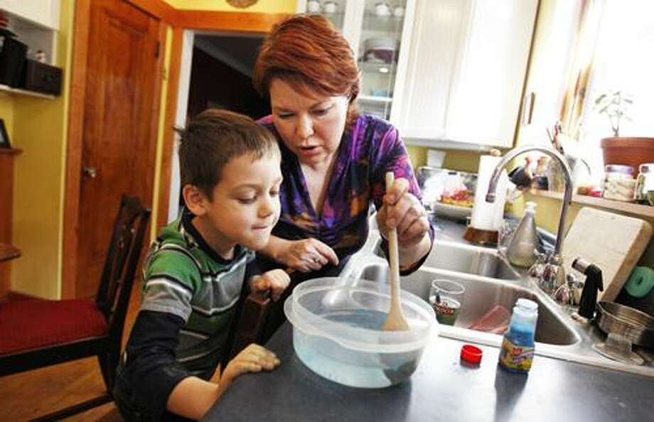 AP Photo Lindsay Porter does weather experiments with her son CJ Kozlowski in their home in Chicago. Photo: AP / AP