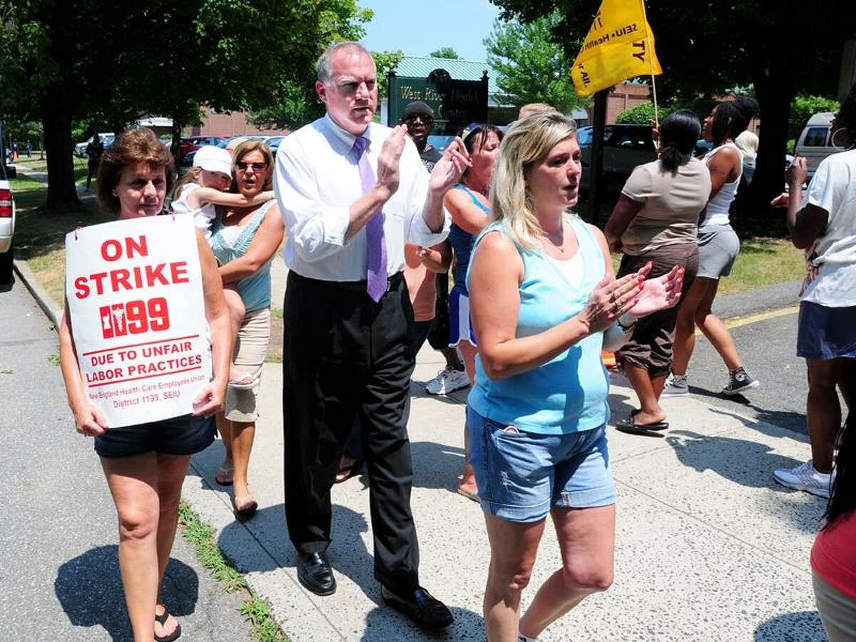Connecticut Attorney General George Jepsen, center left, join strikers protesting in front of the West River Health Care Center on Orange Avenue in Milford. Photo by Arnold Gold/New Haven Register