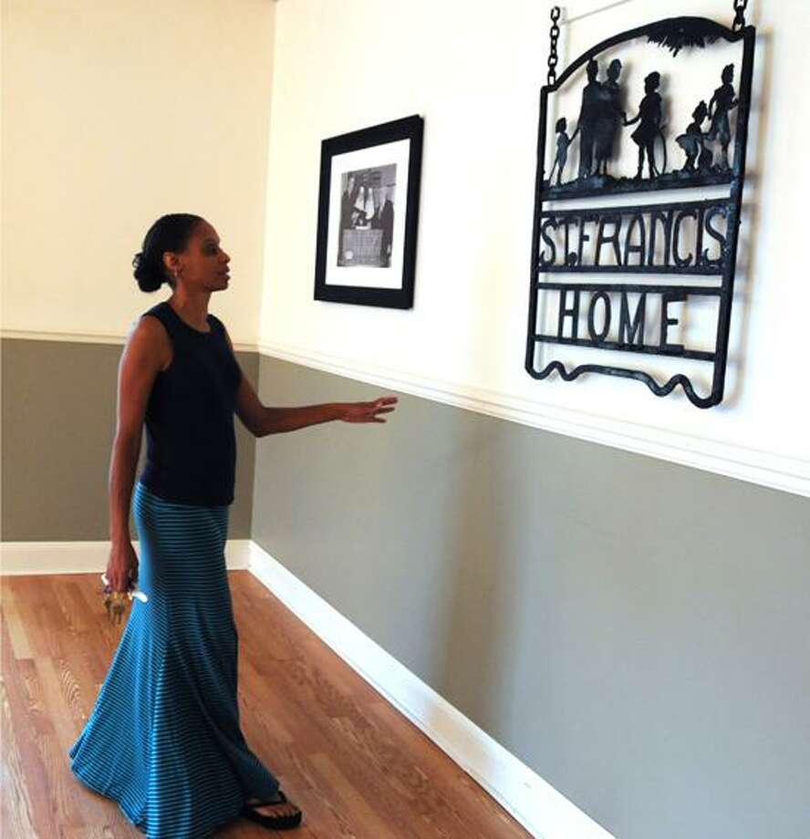 Paula Moody, executive director of the St. Francis Home For Children at 651 Prospect St. in New Haven, shows off a wrought iron sign displayed on a room at the facility.  Peter Hvizdak/New Haven Register Photo: New Haven Register / ©Peter Hvizdak /  New Haven Register