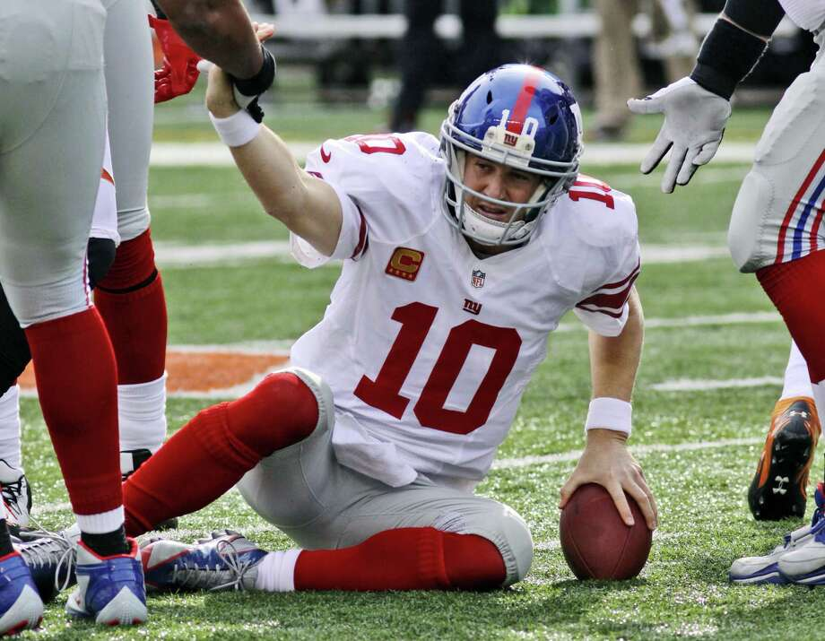 Giants quarterback Eli Manning is helped off the field after getting knocked down during a game against the Cincinnati Bengals.  Photo by Associated Press Photo: ASSOCIATED PRESS / AP2012