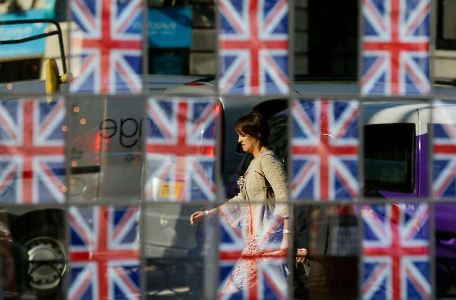 A commuter, seen reflected in the glass of a pub window covered in British flags, walks to work ahead of the 2012 Summer Olympics, Monday, July 23, 2012, in London. (AP Photo/Ben Curtis) Photo: ASSOCIATED PRESS / AP2012