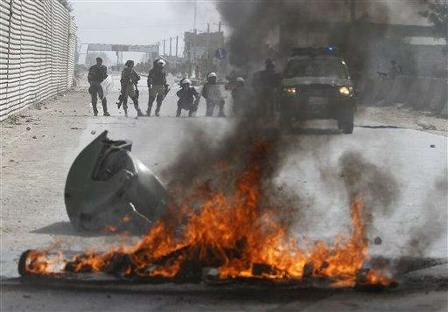 Afghan police stand by burning tires during a protest Monday in Kabul, Afghanistan. Hundreds of Afghans burned cars and threw rocks at a U.S. military base as a demonstration against an anti-Islam film that ridicules the Prophet Muhammad turned violent in the Afghan capital early Monday. Associated Press Photo: AP / AP