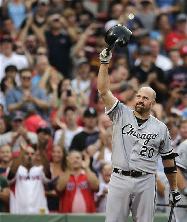 Chicago White Sox third baseman Kevin Youkilis tips his batting helmet to fans as he receives a standing ovation during the first inning of a baseball game against the Boston Red Sox at Fenway Park in Boston, Monday, July 16, 2012. Youkilis returned to Fenway, where he was a member of the 2004 and 2007 World Series Champion teams, for the first time since being traded. (AP Photo/Charles Krupa) Photo: AP / AP