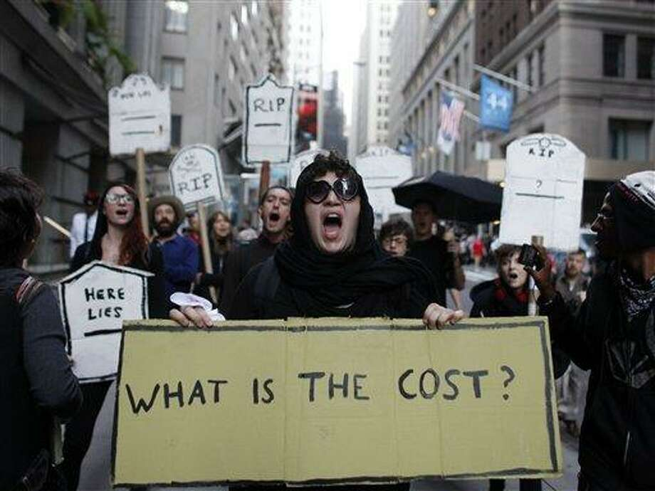 Protestors chant during an Occupy Wall Street march, Monday, Sept. 17, 2012, in New York.  A handful of Occupy Wall Street protestors were arrested during a march on the New York Stock Exchange on the anniversary of the grass-roots movement. (AP Photo/Jason DeCrow) Photo: AP / FR103966 AP