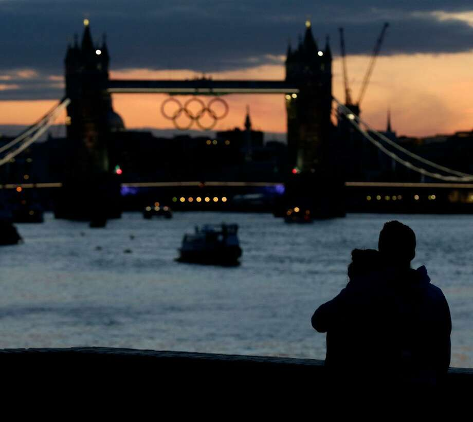 A couple watches the sunset behind the Tower Bridge with the Olympic rings hanging from it Sunday, July 15, 2012, as London prepares for the 2012 Summer Olympics. (AP Photo/Charlie Riedel) Photo: ASSOCIATED PRESS / AP2012
