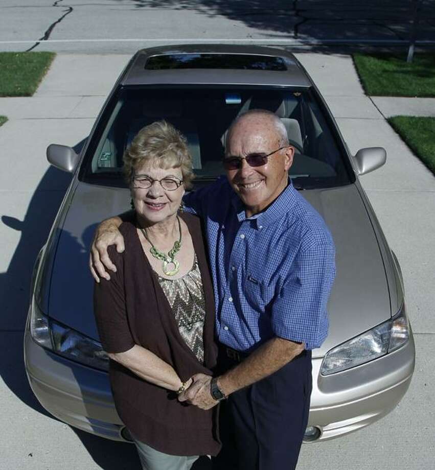 AP Photo Sandy and Jerry Wiseman pose in the driveway with one of their cars in Schaumburg, Ill. Photo: AP / AP