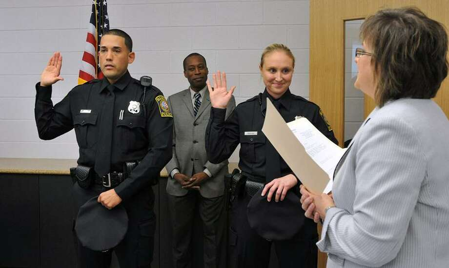 Hamden Assistant Town Clerk, Joanne Cifarelli, swears in the town's newest police officers during a ceremony Thursday afternoon. They are; Kelley Groleau, and Enrique Rivera-Rodriguez. Behind them is Hamden Mayor Scott Jackson. Peter Casolino/New Haven Register