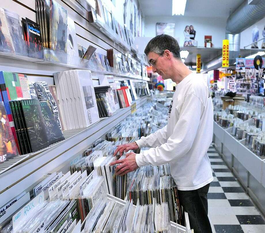 Employee Bob Briar sorts records at Cutler's Record and Tapes, which is closing at the end of June. Briar has worked at the store since 1974, when he was 17 years old. Peter Casolino/New Haven Register
