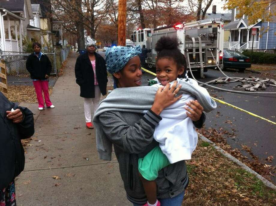 Shay Wells holds her daughter Nataye, 5. They fled their house Tuesday when the fire jumped the alley. William Kaempffer/New Haven Register