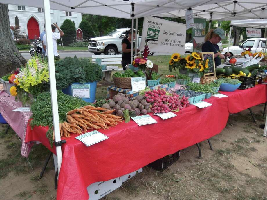 SARAH BOGUES/Register Citizen A vendor's table is laden with fresh produce at the New Hartford Farmers Market Friday.