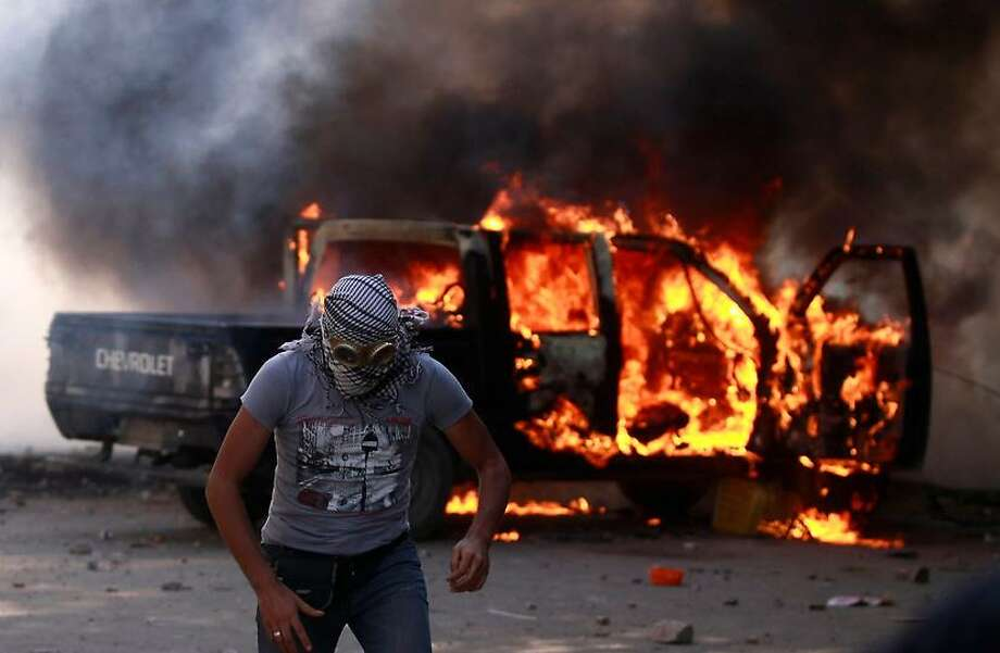 An Egyptian protester runs from a burning police car during clashes with riot police, unseen, near the U.S. embassy Thursday in Cairo, Egypt. Protesters clash with police near the U.S. Embassy in Cairo for the third day in a row. Egypt's Islamist President Mohammed Morsi vowed to protect foreign embassies in Cairo, where police were using tear gas to disperse protesters at the U.S. mission. Associated Press Photo: ASSOCIATED PRESS / AP2012