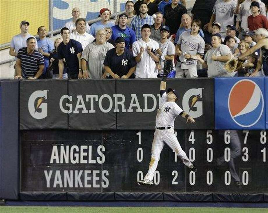 New York Yankees' Nick Swisher catches a ball hit by Los Angeles Angels' Mark Trumbo during the eighth inning of a baseball game, Friday, July 13, 2012, in New York. (AP Photo/Frank Franklin II) Photo: AP / AP