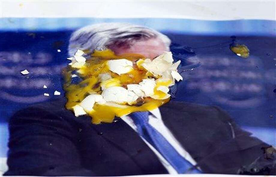 A poster of JPMorgan Chase CEO Jamie Dimon is covered with eggs thrown by protesters, outside the gate of the JPMorgan Chase annual stockholders meeting Tuesday in Tampa, Fla.  Associated Press Photo: AP / FR170674 AP