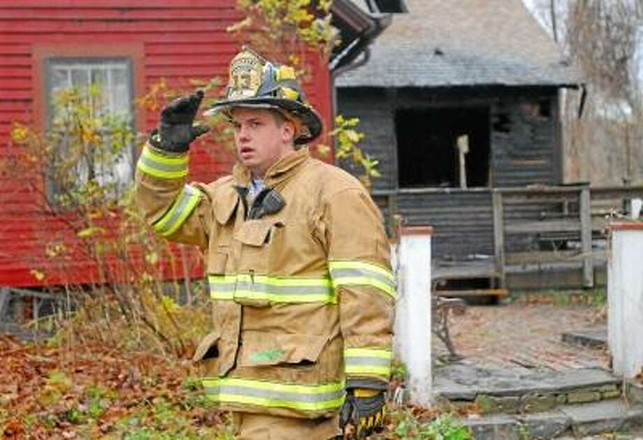 Haddam Fire Lt. Dan Sullivan walks past the nearly 300 year old house on Plains Road in Haddam that was swept by fire early Tuesday morning. Catherine Avalone/The Middletown Press