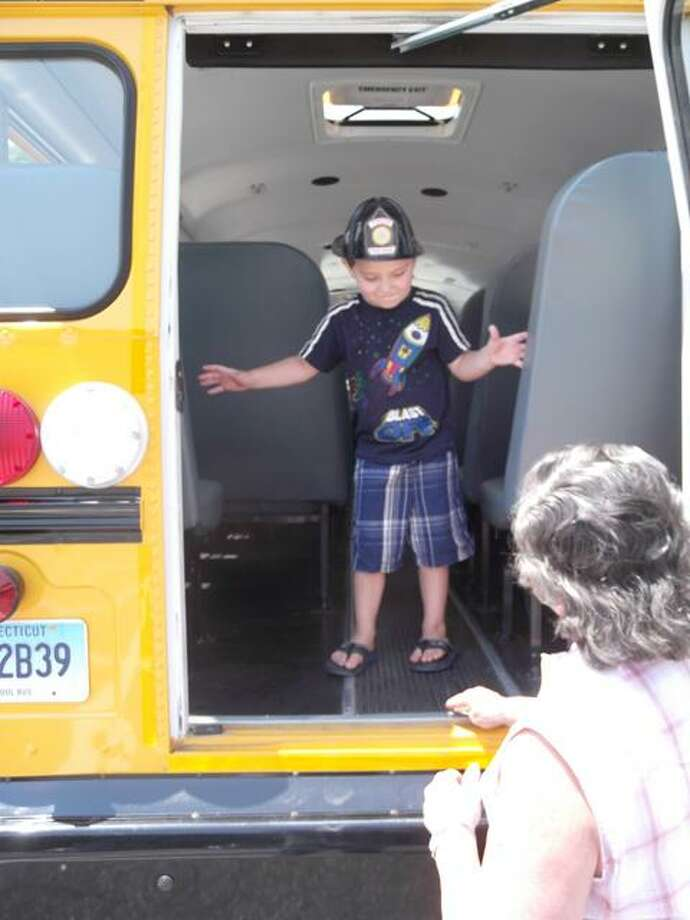 RICKY CAMPBELL/ Register Citizen Four-year-old Jordan from Winsted gets a tour of a school bus Saturday in Winsted. The school bus at Child Safety Day provided an opportunity for children to explore the school bus before they get on it next year.