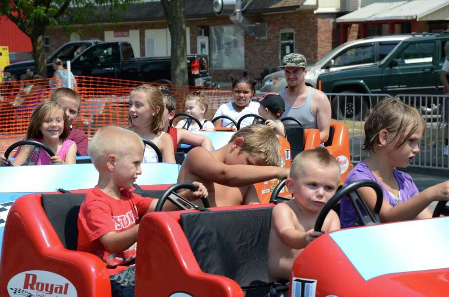 Kids enjoy a breeze on a race car ride Saturday in downtown Oneida during Summer Fest.