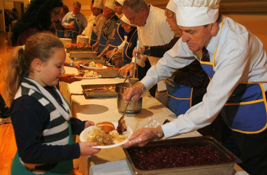 "Dispatch Staff Photo by JOHN HAEGER <a href=""http://twitter.com/oneidaphoto"">twitter.com/oneidaphoto</a> Girl Scout Troop 243 member Haylee Emmons, then-10, holds a plate as Jerry Gortner places cranberry sauce on the plate to be served during the annual Rotary Thanksgiving Dinner on Wed. Nov. 23, 2011 at the Kallet Civic Center in Oneida."