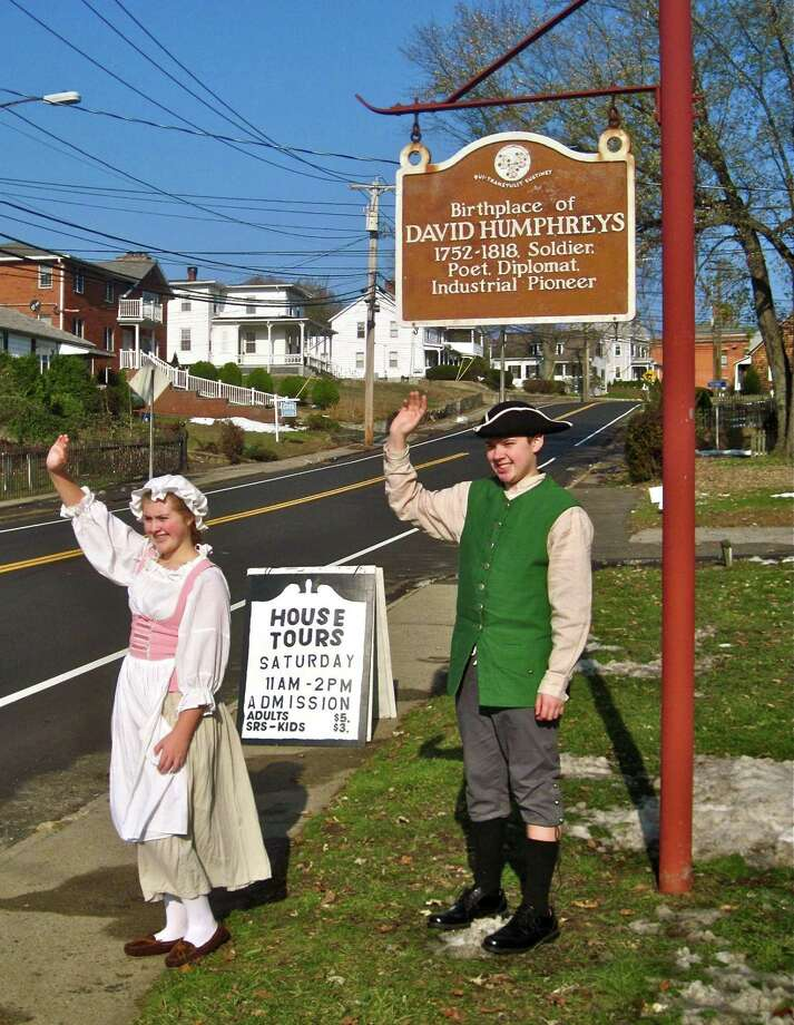 Derby Historical Society junior docents Lauren Fadiman, left, and Quentin Salgado, both 13 and from Shelton, wave to passing motorists Saturday in front of the David Humphreys House, 37 Elm St., Ansonia. The historical society held its annual open-hearth cooking demonstration, featuring Colonial-style Thanksgiving dinner fare. Patricia Villers/Register