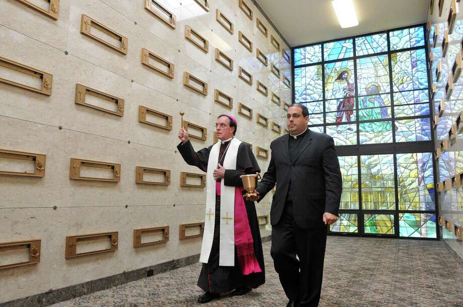 Archbishop Henry J. Mansell, left, sprinkles holy water around the new addition to the mausoleum at Mount Saint Peter Cemetery in Derby. On the right is the Rev. Jeffrey Romans, assistant chancelor.  Photo Peter Casolino/New Haven Register