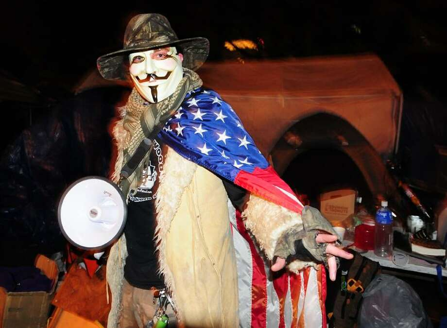 An Occupier in a Guy Fawkes mask makes his way through camp. Occupy New Haven has challenged the group's eviction in court. They invited all interested people to join tonight's party.  Melanie Stengel/Register