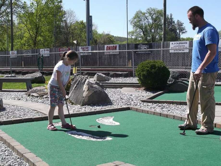 RICKY CAMPBELL/ Register Citizen Jeremy and his daughter Alexis, 7, of Barkhamsted, took to R&B Sports World's mini-golf course Saturday during the annual Winchester Youth Service Bureau's Miniature Golf Event.