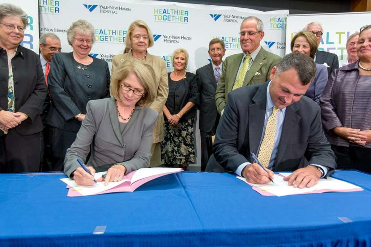 Marna Borgstrom, left and Christopher O'Connor, right, sign the final agreements making official the integration between the two New Haven-based hospitals.
