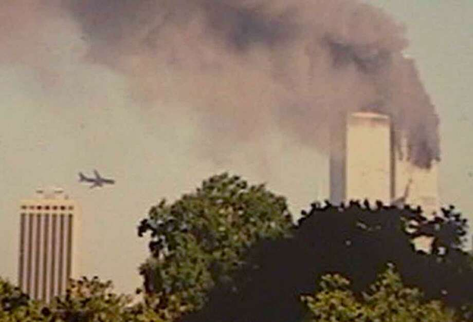 A plane approaches New York's World Trade Center moments before it stuck the tower at left, as seen from downtown Brooklyn, Tuesday, Sept. 11, 2001. In an unprecedented show of terrorist horror, the 110-story towers collapsed in a shower of rubble and dust after two hijacked airliners carrying scores of passengers slammed into them. (AP Photo/William Kratzke) Photo: AP / AP