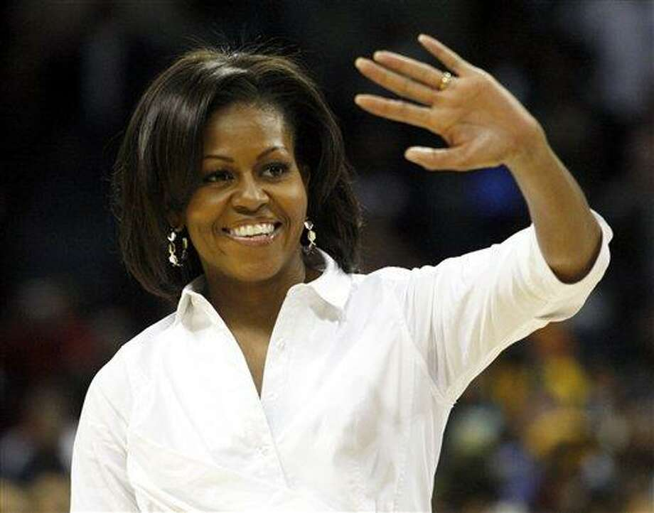 "First Lady Michelle Obama waves during a ""Let's Move!"" physical fitness promotion between games at the CIAA basketball tournament March 2 in Charlotte, N.C. Associated Press Photo: ASSOCIATED PRESS / AP2012"