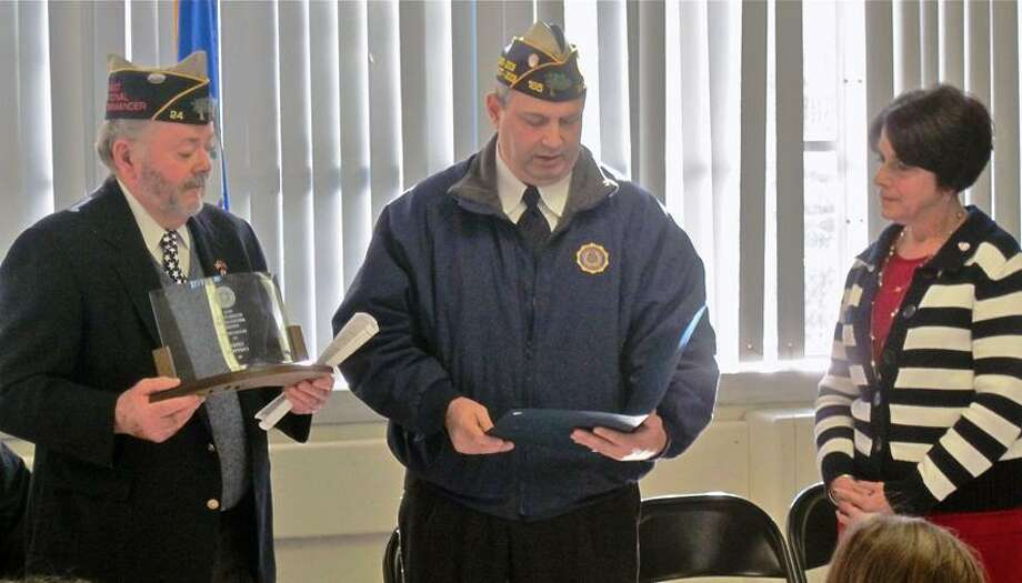 Erwin 'Gus' Williams, commander, John H. Collins Post 24 American Legion of Derby, left, and Harry Hanson of Wolcott, an active-duty member of the Connecticut Air National Guard, present a Community Americanism Award to St. Mary-St. Michael School Principal Linda Coppola Friday at the Derby school.