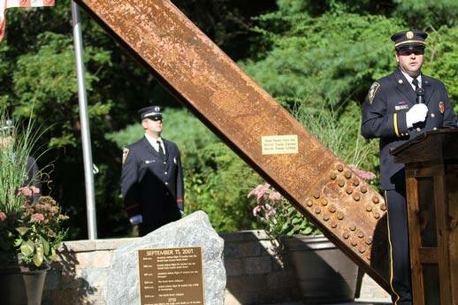 Photo by Marianne Killacky The victims of 9/11 were honored at the North End Firehouse Tuesday, with a brief memorial service in front of a metal beam for the North Tower. / 2012