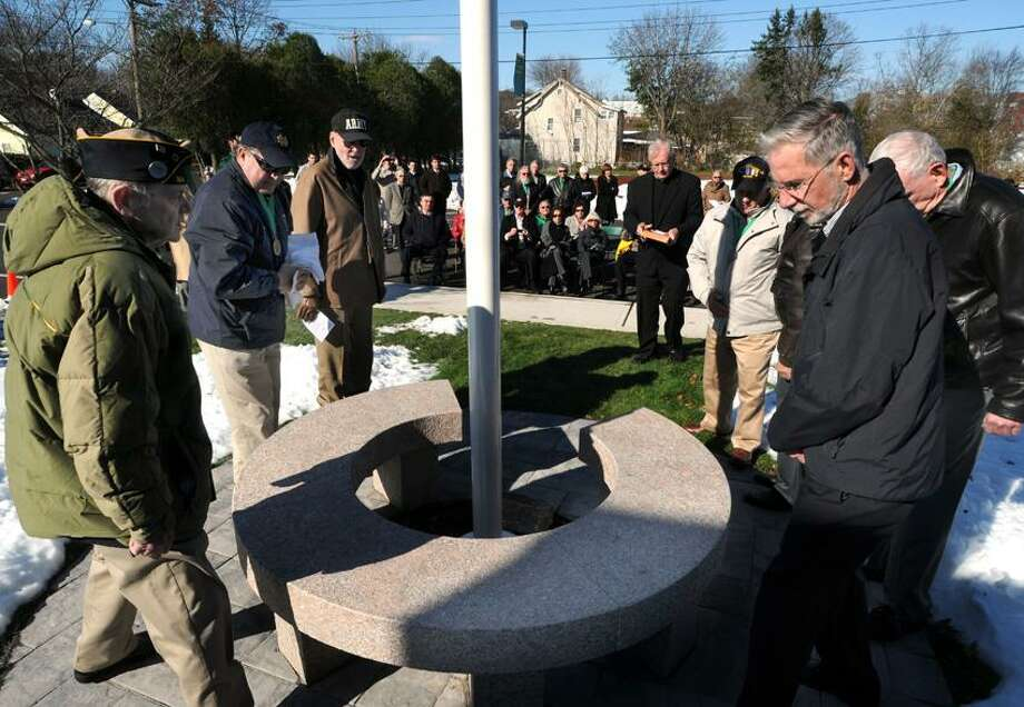 A bench of Stony Creek granite and a bronze plaque were dedicated honoring Richard Regan, a Notre Dame graduate who died in Vietnam, and all Notre Dame veterans, several of whom attended the ceremony. Mara Lavitt/New Haven Register11/9/12