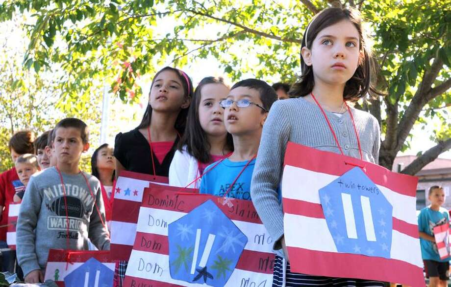 Live Oaks Elementary School second graders including Dominic Rusu with glasses and Maria Korman right during a  9/11 remembrance at the World Trade Center Memorial Garden at the school in Milford. The second graders made WTC posters in art class. Mara Lavitt/New Haven Register