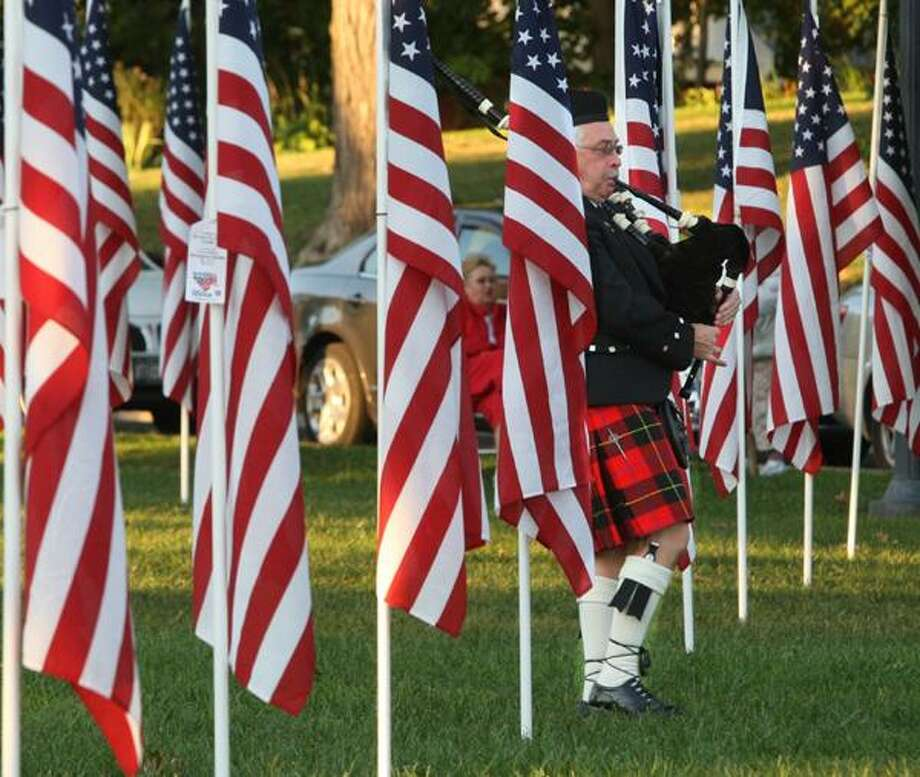 "Dispatch Staff Photo by JOHN HAEGER <a href=""http://twitter.com/oneidaphoto"">twitter.com/oneidaphoto</a> bagpiper Dan Skinner pass through the rows of 258 American Flags at the Sherrill Field of Honor before the start of the 9-11 remembrance service on the 11th anniversary of the attack on Tuesday, Sept. 11, 2012."