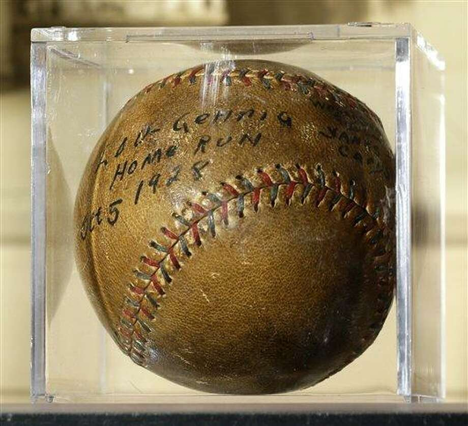 A baseball that New York Yankees slugger Lou Gehrig hit for a World Series home run in 1928 is on display at a convention center in Kansas City, Mo., Thursday, July 5, 2012. Stamford, Conn., resident Elizabeth Gott is selling the baseball at auction on behalf of her 30-year-old son, Michael, to help pay off his medical school debts. (AP Photo/Charlie Riedel) Photo: AP / AP