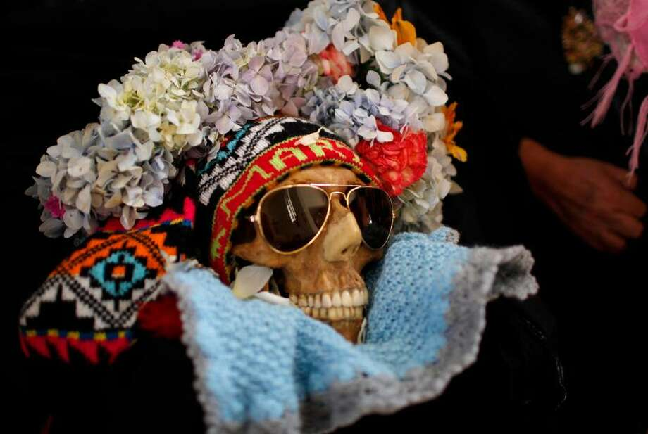 "A decorated human skull or Natita is carried out of the Cementerio Generalís chapel and to the Natitas Festival at the largest cemetery in La Paz, Bolivia, Thursday, Nov. 8, 2012. ""Natitas,"" are human skulls from unnamed, abandoned graves that are cared for and decorated by faithful who use them as amulets believing they serve as protection from thieves. The festival is a mixture of Andean ancestral worship rites and Catholic beliefs. According to experts, it was common practice in the pre-Hispanic era to keep skulls as trophies and display them during the rituals to symbolize death and rebirth. The festival marks the end of the All Saintsí holiday, but is not recognized by the Catholic church. (AP Photo/Juan Karita) Photo: ASSOCIATED PRESS / AP2012"